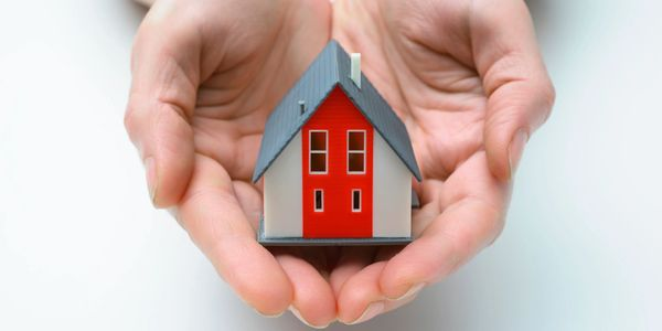 Small house in hands.